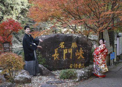 長門峡と書かれた安倍晋三総理揮毫石碑の前で結婚写真記念写真